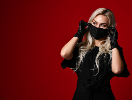 Beautiful woman in protective black medical mask and gloves on dark red background looking at the corner with free text space Stok Fotoğraf