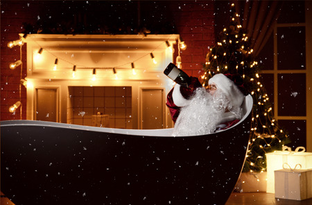 Bad Santa Claus drinking champagne alcohol from the bottle in big bathtub with christmas tree interior and fireplace background decoration with retro light bulbs . New year Holidays celebration concept