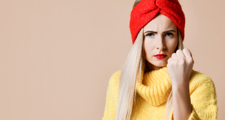 Aggressive woman show fist ready to fight expression emotion in fashion sunglasses yellow sweater and red lips on beige background