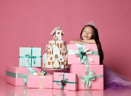 Little asian girl in crown and purple dress with many present gift boxes and ginger cookie cake birthday celebration dreaming on pink background