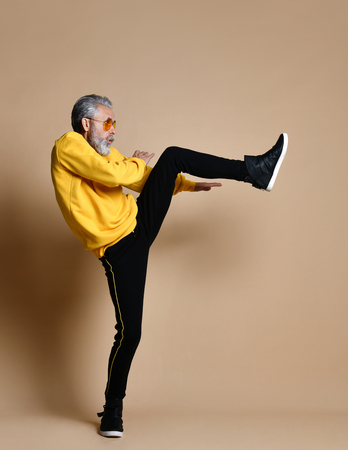 Old brutal senior millionaire man in yellow cloth and aviator stylish sunglasses exercise stretching hit punch with leg  on beige background
