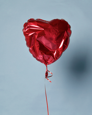 Party is over deflated red heart balloon object for birthday party or love valentines day on light blue background