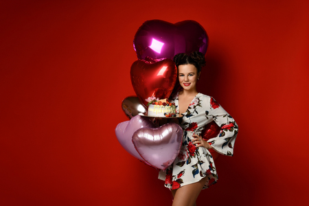 Young woman hold big sweet cake with strawberry blueberry and cream smiling celebrating birthday with balloons on dark red background Zdjęcie Seryjne