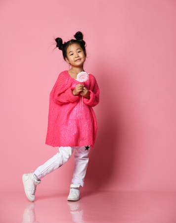 Happy young asian little girl kid lick eat happy big sweet lollypop candy on pink background