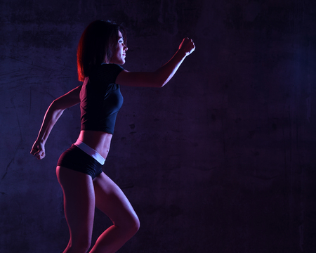 Young sport woman running jogging in gyn in blue and pink neon light on dark wall background Stock Photo
