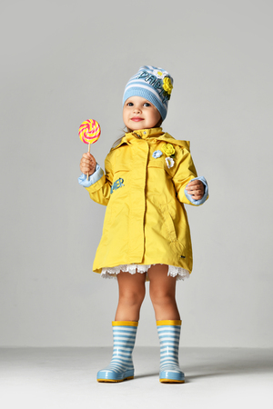 Young pretty toddler girl kid with big sweet lollypop candy in yellow jacket and rubber boots on grey background