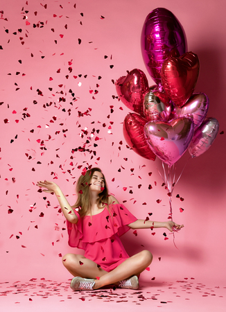 Valentine Beauty girl hold red and pink air balloons laughing on pink background. Beautiful Happy Young woman holiday party joyful having fun celebrating Valentines Day Stock Photo