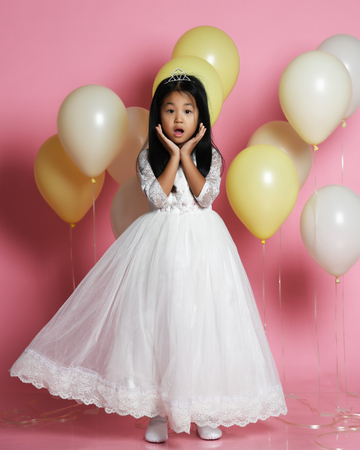Surprised asian kid girl with balloons in princess dress with tiara princess crown. Pink background.
