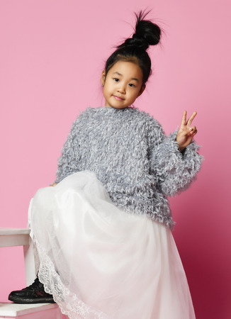 Young asian girl kid in long white skirt, grey fluffy sweater and black shoes with foot on the step. Show victory. Smiling. On pink background. 免版税图像