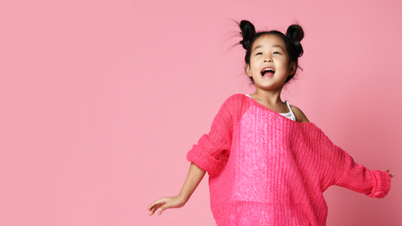 Asian kid girl in pink sweater, white pants and funny buns sings happy smiling on pink background