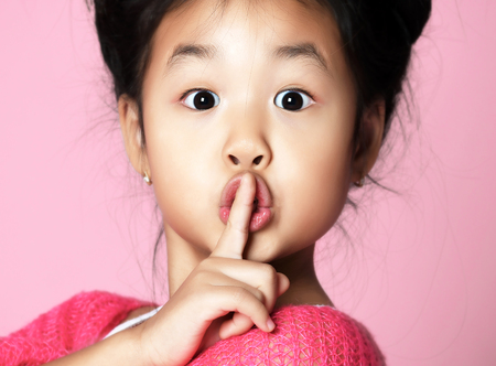 Asian kid girl in pink sweater shows shhh quiet sign on pink background