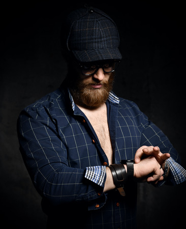 Stylish bearded man in plaid shirt, Scherlock plaid cap and leather wristband look at his wrist watch