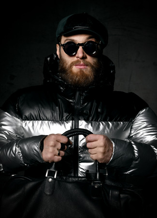 Brutal bearded man in silver winter jacket, cap hat and round modern sunglasses holds bag