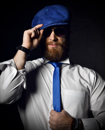 Stylish bearded man in white shirt and sunglesses holds his blue cap hat and tie greeting