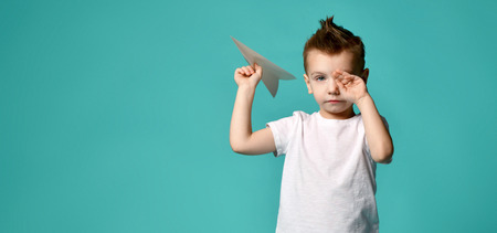 Little boy ready to launch a paper plane but stopped to rub eye with hand on popular green. new step. hard start. free text space Stock Photo