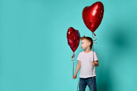 Little boy love hold big red heart balloon to celebrate valentines day and upset by another deflated red heart balloon on popular green with free text space Stock Photo