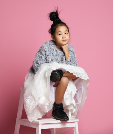 Young asian girl kid in long white skirt, grey fluffy sweater and black shoes sits legs crossed on pink background