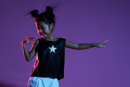 Joyfull asian kid girl in shirt and pants with stars and on purple background dance