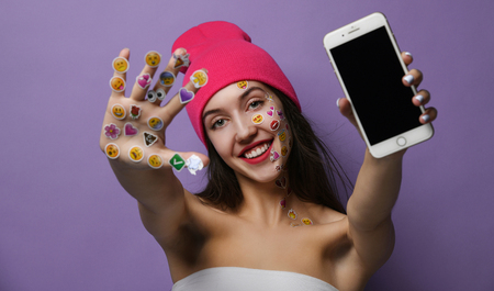 Young woman with popular social mobile emoji smiles stickers for cellphone on her hands happy smiling laughing showing blank display screen Stockfoto