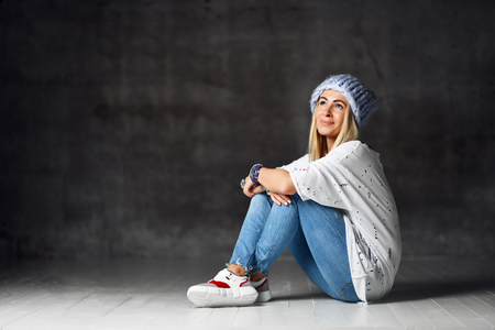Blonde woman in light blue knitted hat and jeans happy smiling sitting posing on dark background