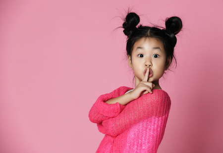 Asian kid girl in pink sweater shows shh sign on pink background. Close up portrait 免版税图像