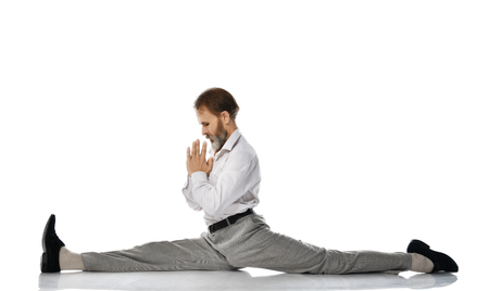 Old man practicing yoga classic asana pose do the splits against white background Stockfoto