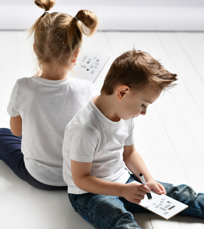 two kids boy and girl in white t-shirts and blue jeans sit close to each other and play battleship on white wooden floor Stock Photo