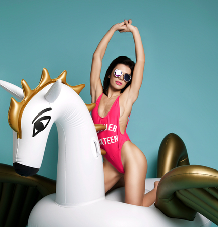 Young fashion woman relaxing with big inflatable unicorn pegasus float mattress in sexy pink bikini for swimming pool on blue mint background Stockfoto