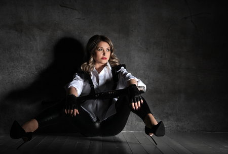 Young sensual mature beautiful sexy woman posing in white man shirt and high-heeled shoes on dark background Stok Fotoğraf