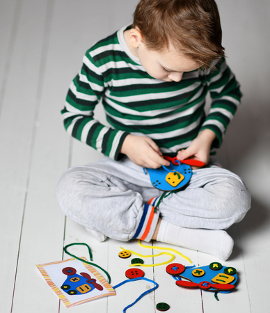 Kid boy plays educational game interestedly with wooden colorful blue helicopter and laces on white background
