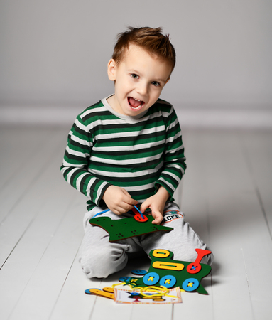 Happy kid boy enjoys playing educational game with wooden colorful train and laces on white background Imagens