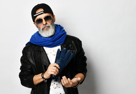 Old brutal senior rich man in leather jacket blue and red baseball cap and long blue scarf stands with gloves in arms stylish fashionable men isolated on white background