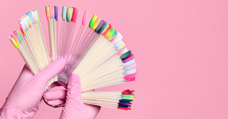 Hand hold pedicure and manicure samples for nails salon and spa brush nail on pink background