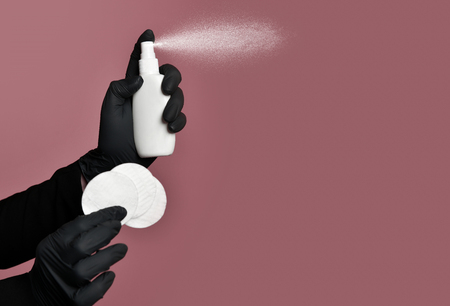 Doctor cosmetician keeps in hands bottle with spray dispenser and cotton pad on beige background close-up