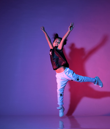 Joyfull asian kid girl in shirt and pants with stars on purple background dances and jumps