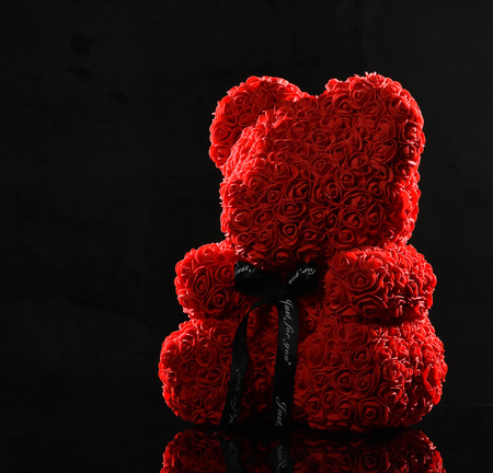 Red bear of roses present gift for valentines day or woman birthday on dark