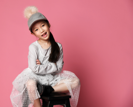 Nicely smiling asian fashion kid girl in pink dress and funny cap with fur pompon on pink background with free text space Foto de archivo - 117303838
