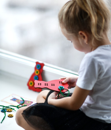 Kid girl plays educational game interestedly with wooden colorful bear and laces sitting near window Stockfoto