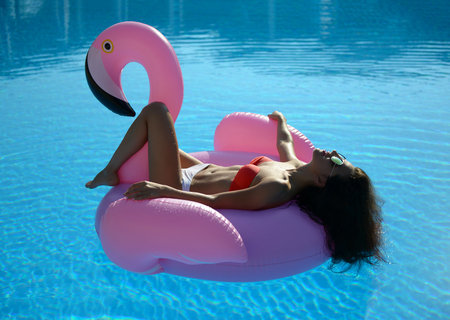 Young sexy pretty woman relaxing in a swimming pool leisure on a giant inflatable giant pink flamingo float mattress in red bikini Stockfoto