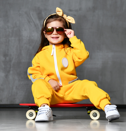 Cool kid girl in yellow hooded jumpsuit costume, sunglasses and killing yellow bow sits on cool red skateboard with playful smile on grey background