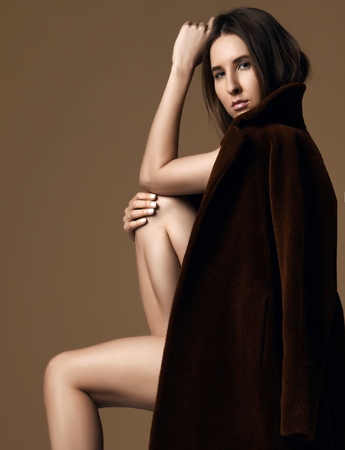 Young beautiful hipster girl sitting thinking  sexy in brown spring jacket naked on beige background Stockfoto