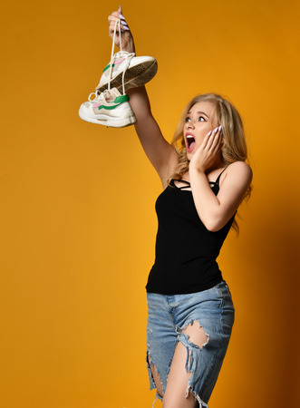 Young blonde girl is horrified by old pair of dirty shoes on yellow background. She cant believe it is so bad