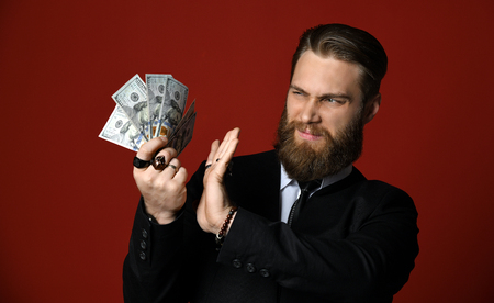 Stylish bearded business man hand holding American dollars hundreds banknotes bu treat it with suspicious and to fence off by a hand on red background Фото со стока