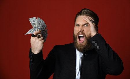 Business man in black suit and whit shirt holds American dollars hundreds banknotes and shouts loudly