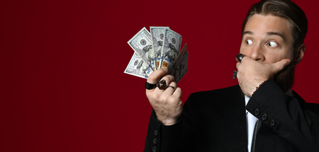 Business man hand holding American dollars  hundreds banknotes scary close mouth with hand on red