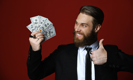 Business man in suit hand holding American dollars banknotes show thumb up sign on red