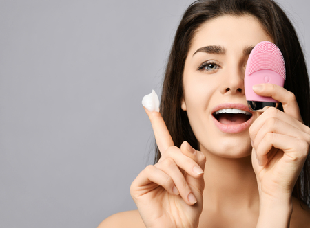 Young woman covers her eye with pink face brush silicone cleansing device for skin, shows cream on finger and smiles happily. Background. Text space. Stock Photo