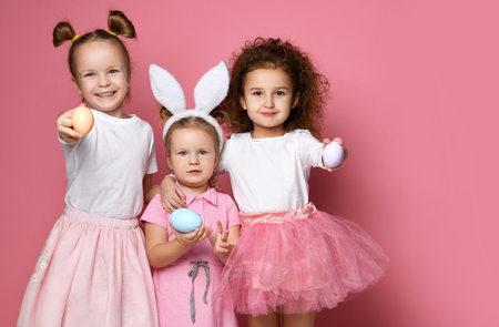 Three smiling dressed up for the holiday kid girls with painted eggs on Easter day. Happy Easter concept holiday celebration on pink background Stock Photo - 120352716