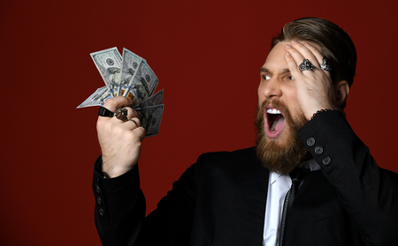 Business man in black suit and whit shirt holds American dollars hundreds banknotes, looks at it and shouts loudly Oh, My God  on red background