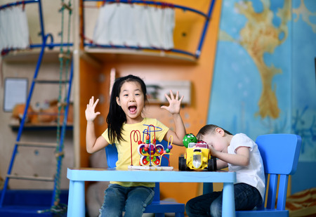 Two joyful  kids preschoolers boy and girl play enthusiastically at the table with toys on playroom background